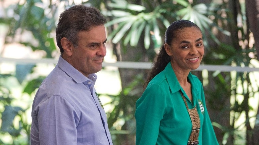 Aecio Neves, who is running for president with the Brazilian Social Democracy Party, left, stands with his former rival candidate Marina Silva, of the Brazilian Socialist Party, who supported his candidacy after she finished third in the first-round of elections, at a campaign event in Sao Paulo, Brazil, Friday, Oct. 17, 2014. Neves will face Brazil's President Dilma Rousseff in a presidential runoff on Oct. 26. (AP Photo/Andre Penner)