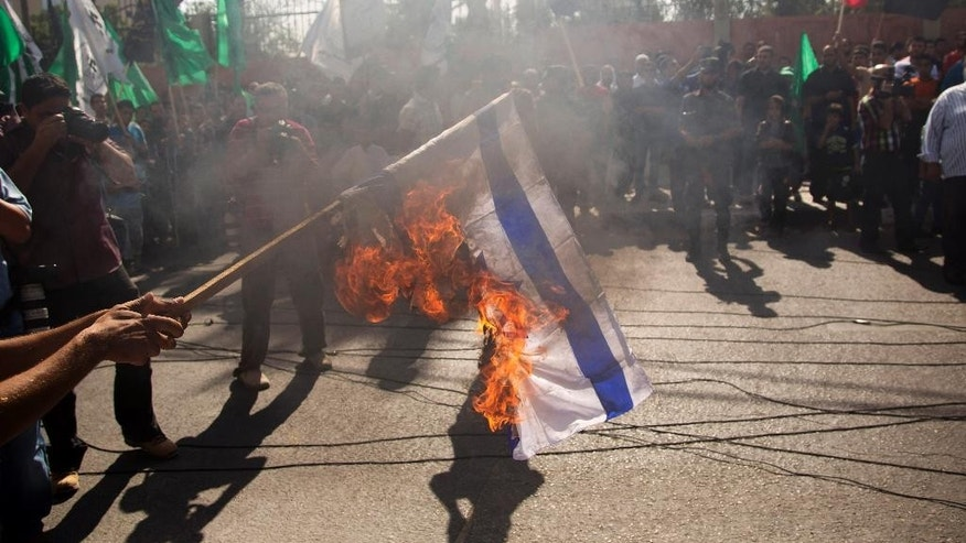 A Palestinian demonstrator burns the Israeli flag, invoking the Al-Aqsa mosque in Jerusalem, where Israel is limiting access to Palestinian worshippers, as he and others hold a rally in Gaza City, Friday, Oct. 17, 2014. (AP Photo/Khalil Hamra)