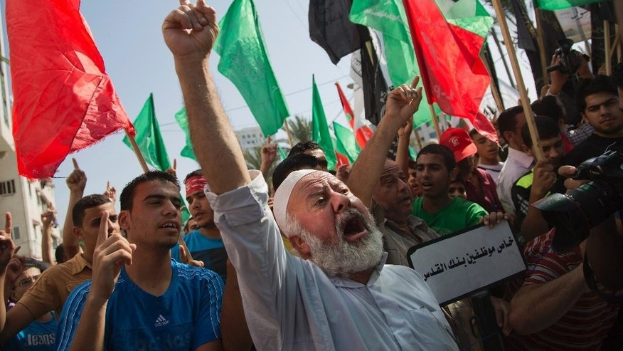 Palestinians chant slogans invoking the Al-Aqsa mosque in Jerusalem, where Israel is limiting access to Palestinian worshippers, while holding a rally in Gaza City, Friday, Oct. 17, 2014. (AP Photo/Khalil Hamra)