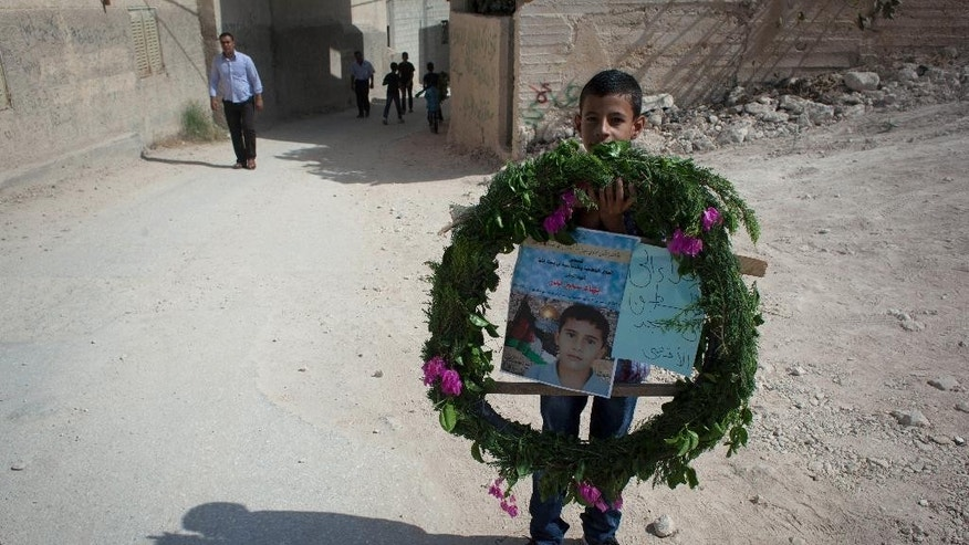 "A boy carries a wreath with posters with a photo of slain Palestinian boy Baha Samir Bader, 13, ahead of his funeral procession at the village of Beit Lykia near the West Bank city of Ramallah, Friday, Oct. 17, 2014. Palestinian police said that the boy has been shot dead by Israeli soldiers during a clash in the village. Tensions between Israelis and Palestinians have spiked in recent days amid Palestinian charges that Israel is limiting access to Palestinian worshippers at a sensitive Jerusalem holy site. The poster reads the slain boy's name in Arabic and ""a sacrifice for Palestine and the al-Aqsa mosque."" (AP Photo/Nasser Nasser)"