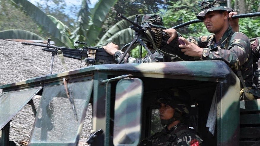 Philippine soldiers head to the mountains to secure the release of two Germans who were held for six months by the Abu Sayyaf militant group, on the volatile island of Jolo, southern Philippines, Friday, Oct. 17, 2014. Philippine Defense Secretary Voltaire Gazmin said the group released Stefan Okonek and Henrike Dielen late Friday on southern Jolo Island. (AP Photo/Nickee Butlangan)