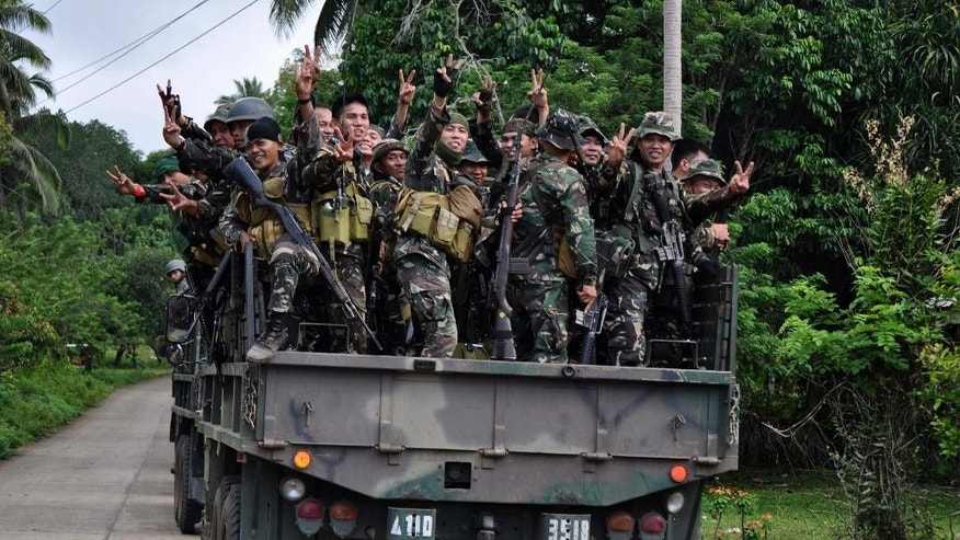 Philippine soldiers wave to the media as they head to the mountains to secure the release of two Germans who were held for six months by the Abu Sayyaf militant group, on the volatile island of Jolo, southern Philippines, Friday, Oct. 17, 2014. Philippine Defense Secretary Voltaire Gazmin said the group released Stefan Okonek and Henrike Dielen late Friday on southern Jolo Island. (AP Photo/Nickee Butlangan)