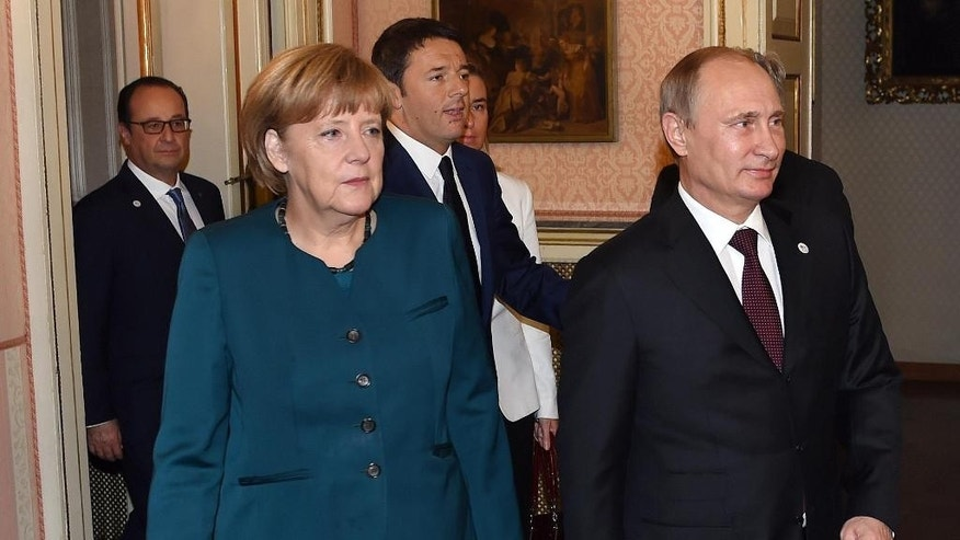 German Chancellor Angela Merkel, front left, Russian President Vladimir Putin, right, Italian Prime Minister Matteo Renzi, center, and French President Francois Hollande arrive for a meeting on the sidelines of the  ASEM summit of European and Asian leaders in Milan, northern Italy, Friday, Oct. 17, 2014. Russian President Vladimir Putin is looking to get relief from Western economic sanctions imposed since Russia's annexation of the Crimean Peninsula and its support for a pro-Russia insurgency in eastern Ukraine. To that end, he has scheduled a series of meetings on the sidelines of a two-day ASEM summit of European and Asian leaders. (AP Photo/Daniel Dal Zennaro, POOL)