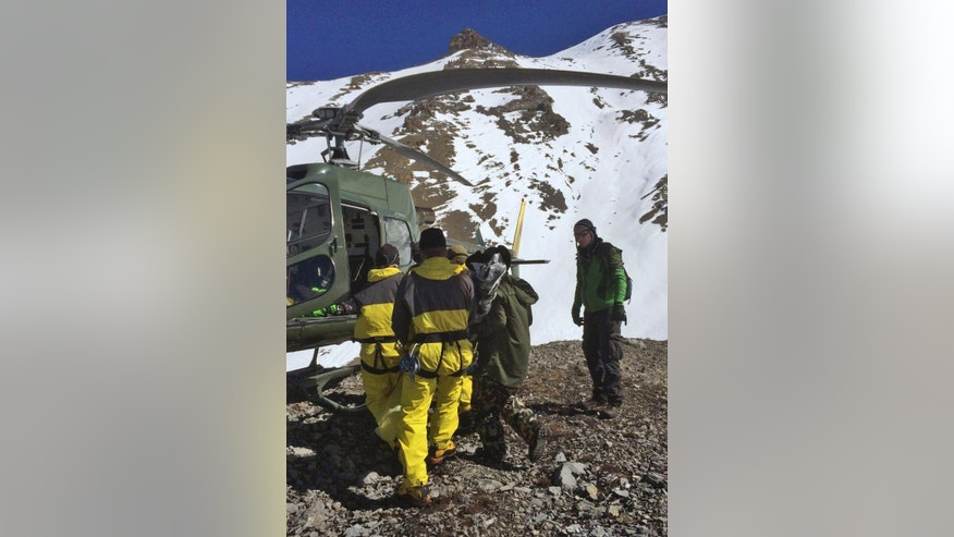 In this Thursday, Oct. 16, 2014 photo provided by the Nepalese army, rescue personnel carry a victim of an avalanche before they airlift the body from Thorong La pass area, in Nepal. Rescuers widened their search Friday for trekkers stranded since a series of blizzards and avalanches battered the Himalayas in northern Nepal early this week leaving at least 29 people killed, officials said. (AP Photo/Nepalese Army)