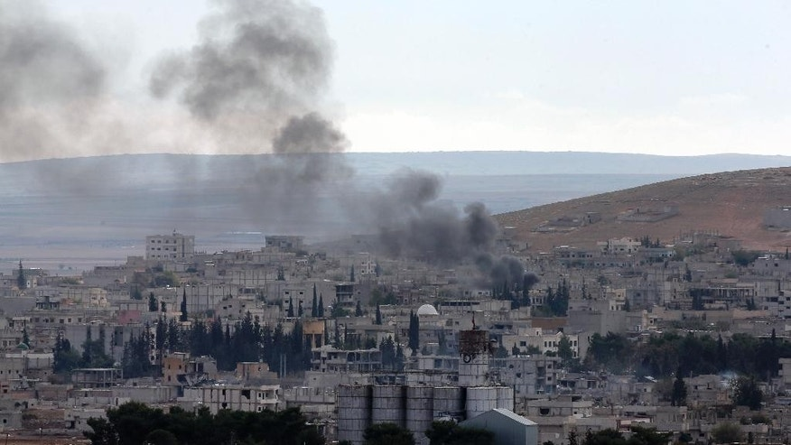 Smoke from a fire rises in Kobani, Syria while fighting continued between Syrian Kurds and the militants of the Islamic State group, as seen from Mursitpinar on the outskirts of Suruc, at the Turkey-Syria border, Saturday, Oct. 18, 2014. Kobani, also known as Ayn Arab, and its surrounding areas, has been under assault by extremists of the Islamic State group since mid-September and is being defended by Kurdish fighters. (AP Photo/Lefteris Pitarakis)