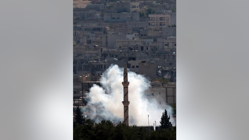 Smoke from a mortar rises in Kobani, Syria while fighting continued between Syrian Kurds and the militants of the Islamic State group, as seen from Mursitpinar on the outskirts of Suruc, at the Turkey-Syria border, Saturday, Oct. 18, 2014. Kobani, also known as Ayn Arab, and its surrounding areas, has been under assault by extremists of the Islamic State group since mid-September and is being defended by Kurdish fighters. (AP Photo/Lefteris Pitarakis)