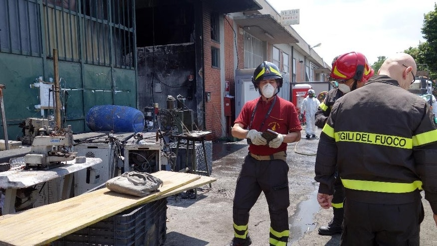 In this June 20, 2014 photo, firemen inspect the burned Teresa Moda garment factory in Prato, Italy. The fire that destroyed the Teresa Moda factory on Dec. 1, 2013, was the deadliest in living memory. It exposed the true cost of cheap clothes, laying bare the consequences of years of failed law enforcement and the pursuit of profit over safety. (AP Photo/Erika Kinetz)