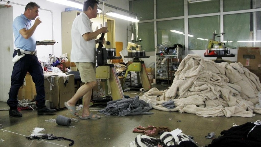 In this June 19, 2014 photo, a police officer, left, inspects a sequestered textile factory in Prato, Italy. The compound, which had been divided into four different factories, was closed because of illegal bedrooms, too few fire extinguishers, no well-marked, easily accessible fire exits, no first aid kit and a dozen gas canisters found during the raid. Of the 44 workers at the factory, 35 were without proper contracts or social security contributions, and six did not have the legal right to stay in Italy. (AP Photo/Fabrizio Giovannozzi)