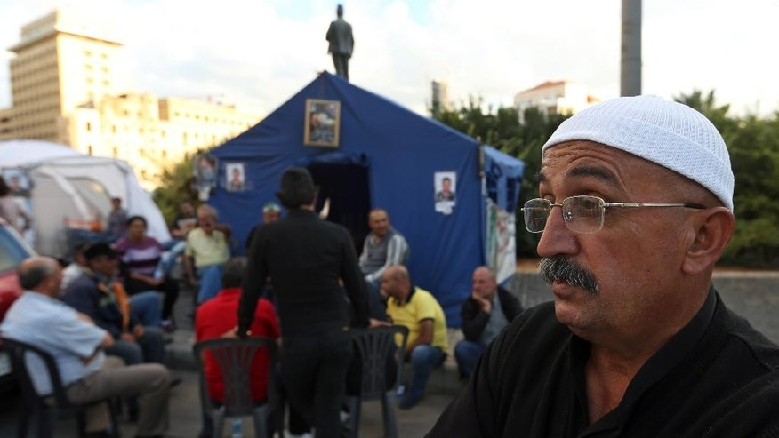 In this Thursday, Oct. 16, 2014 photo, Hamza Hommos, 55, father of Lebanese policeman Wael Hommos, who was kidnapped by Islamic State militants and the Nusra Front, speaks during an interview with The Associated Press in front of his tent set up for their sit-in protest in downtown Beirut, Lebanon. With all eyes on the Islamic State group's onslaught in Iraq and Syria, a less conspicuous but potentially just as explosive frontline with the extremists is emerging in Lebanon, where Lebanese soldiers and Shiite Hezbollah guerrillas are increasingly pulled into deadly fighting with the Sunni militants along the country's border with Syria. (AP Photo/Bilal Hussein)