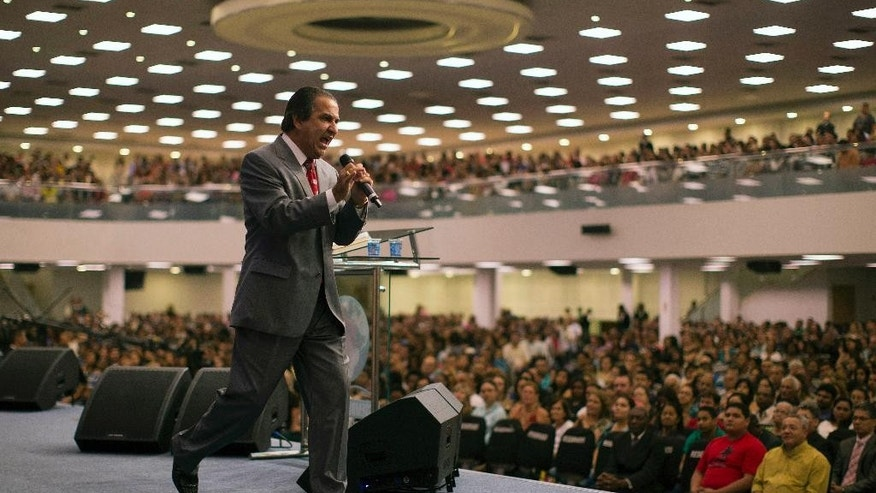 In this Sept. 25, 2014 photo, Brazil's most influential Pentecostal pastor Silas Malafaia, crosses the stage as he preaches during a service at the Assemblies of God church, in Rio de Janeiro, Brazil. Malafaia has 800,000 followers on Twitter, books that have sold in the millions and sermons beamed around the globe. Evangelical lawmakers are at the heart of Brazilís growing conservatism, and theyíve shown an ability to rally the other groups behind their main cause: defeating any attempt to legalize gay  marriage or advance protections of LGBT communities. (AP Photo/Leo Correa)