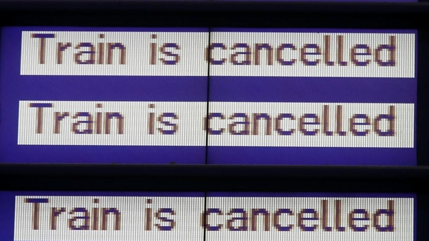 An electronic board flashes cancellation of scheduled passenger trains as German train drivers went on strike to demand pay hike and better work conditions in Frankfurt, Germany, Saturday, Oct. 18, 2014. A union representing German train drivers has called members out on a two-day strike this Saturday and Sunday, escalating a bitter pay dispute with national railway Deutsche Bahn. (AP Photo/Michael Probst)
