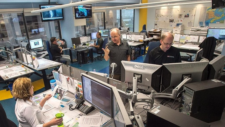 Meteorologists work at the Canadian Hurricane Centre, tracking Hurricane Gonzalo, in Dartmouth, Nova Scotia, Friday, Oct. 17, 2014. Forecasters said there is a possibility of Gonzalo making landfall in the southeastern tip of Newfoundland and Labrador on Sunday. Hurricane Gonzalo roared toward Bermuda as a powerful Category 3 storm on Friday and the head of the tiny British territory urged people to seek high ground due to a potential storm surge of 10 feet. (AP Photo/The Canadian Press, Andrew Vaughan)