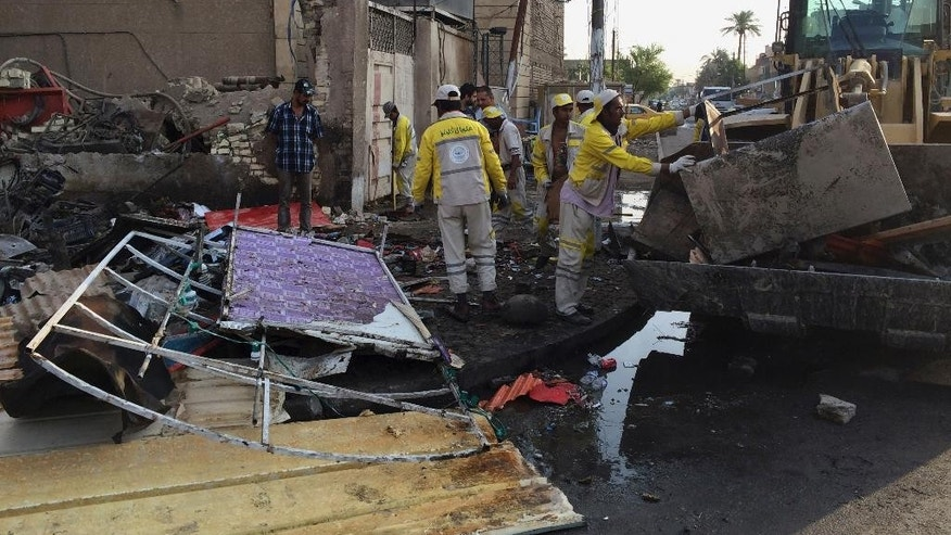 Iraqi municipal government workers clean up debris following a car bomb explosion in central Baghdad's busy commercial Karradah neighborhood, Iraq, Saturday, Oct. 18, 2014. The car bomb exploded after nightfall Friday, near a cafe, killed and wounded tens of people, Iraqi officials said. (AP Photo/Khalid Mohammed)