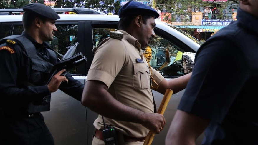 Security personnel escort former chief minister of Tamil Nadu state Jayaram Jayalalitha as she travels in a car after being released from prison in Bangalore, India, Saturday, Oct. 18, 2014. India's top court Friday granted temporary bail to a charismatic southern Indian politician who was sentenced to four years in prison for corruption last month. (AP Photo/Aijaz Rahi)
