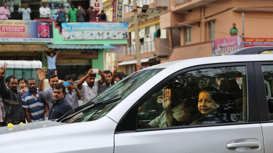 Former chief minister of Tamil Nadu state Jayaram Jayalalitha waves to supporters as she travels in car after being released from prison in Bangalore, India, Saturday, Oct. 18, 2014. India's top court Friday granted temporary bail to a charismatic southern Indian politician who was sentenced to four years in prison for corruption last month. (AP Photo/Aijaz Rahi)