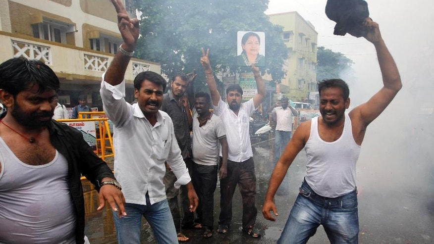Supporters of former chief minister of Tamil Nadu state Jayaram Jayalalitha, a former movie star, hold her portrait and celebrate with firecrackers outside their party office in Chennai, India, Friday, Oct. 17, 2014. India's top court Friday granted temporary bail to the charismatic southern Indian politician who was sentenced to four years in prison after being found guilty of corruption last month. The 65-year-old requested bail because she said she suffered from diabetes and high blood pressure and needed medical attention. (AP Photo/Arun Sankar K)