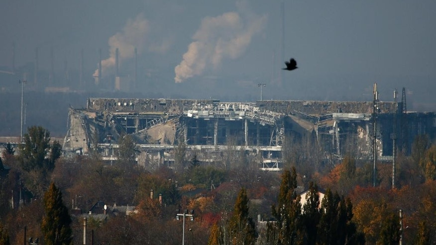 The normally functioning Avdeyevsky chemical plant is seen behind the main terminal of Donetsk Sergey Prokofiev International Airport hit by shelling during artillery battles between pro-Russian rebels and Ukrainian government forces in the town of Donetsk, eastern Ukraine Friday, Oct. 17, 2014. Ukraine's president on Friday hailed progress in Europe-brokered talks aimed at ensuring peace with Russia, with agreements nearing on a gas dispute and local elections in the east. (AP Photo/Dmitry Lovetsky)