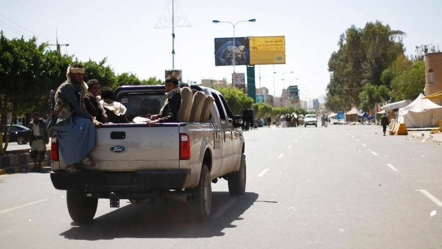 Houthi Shiite rebels riding on a pickup truck, patrol a street while other members dismantle a protest camp on a road leading to the Sanaa Airport in Sanaa, Yemen, Friday, Oct. 17, 2014. Yemeni security officials say fierce clashes have erupted between Shiite rebels in control of the capital and tribesmen allied with the country's Islamist Islah party, leaving eight dead. (AP Photo/Hani Mohammed)