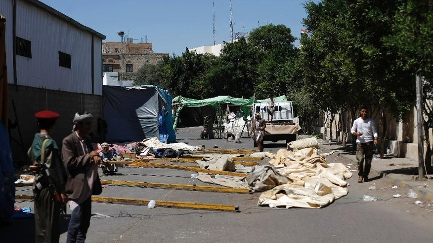 Houthi Shiite rebels remove a tent that was erected two months ago, at a sit-in at a main road leading to the airport in Sanaa, Yemen, Friday, Oct. 17, 2014. Yemeni security officials say fierce clashes have erupted between Shiite rebels in control of the capital and tribesmen allied with the country's Islamist Islah party, leaving eight dead. (AP Photo/Hani Mohammed)
