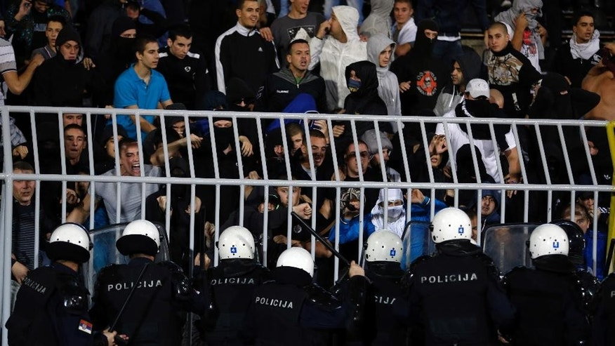 Serbian riot police officers clash with Serbian national team supporters during the Euro 2016 Group I qualifying match between Serbia and Albania at the Partizan stadium in Belgrade, Serbia, Tuesday, Oct. 14, 2014. The 2016 European Championship qualifier between Serbia and Albania was abandoned on Tuesday after skirmishes broke out on the pitch involving players and fans over an Albanian flag that was flown above the stadium by a drone. (AP Photo/Marko Drobnjakovic)