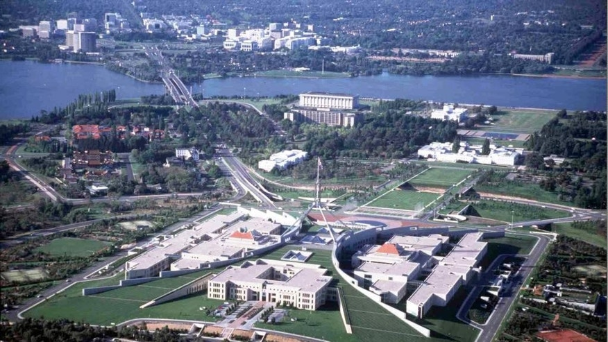 FILE - This undated aerial photo shows Parliament House in Canberra, Australia, and the downtown area at the top. Australia's Parliament House on Monday, Oct. 20, 2014 lifted a short-lived ban on facial coverings including burqas and niqabs after the prime minister intervened. (AP Photo/Canberra Tourism)