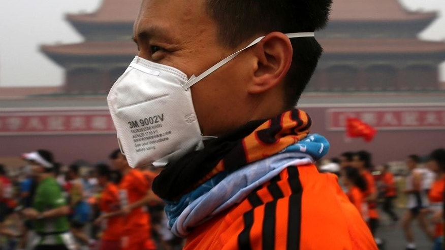 A runner, wearing a mask to protect himself from pollutants, jogs past Tiananmen Gate shrouded in haze while taking part in the 2014 Beijing International Marathon in Beijing, China Sunday, Oct. 19, 2014. (AP Photo/Andy Wong)