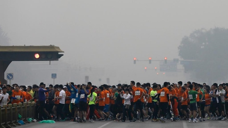 Runners jog past Chang'an Avenue near Tiananmen Square shrouded in haze at the start of 2014 Beijing International Marathon in Beijing, China Sunday, Oct. 19, 2014. (AP Photo/Andy Wong)