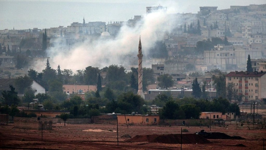 Smoke rises following a strike in Kobani, Syria, during fighting between Syrian Kurds and the militants of Islamic State group, as seen from a hilltop on the outskirts of Suruc, at the Turkey-Syria border, Sunday, Oct. 19, 2014. Kobani, also known as Ayn Arab, and its surrounding areas, has been under assault by extremists of the Islamic State group since mid-September and is being defended by Kurdish fighters. (AP Photo/Lefteris Pitarakis)