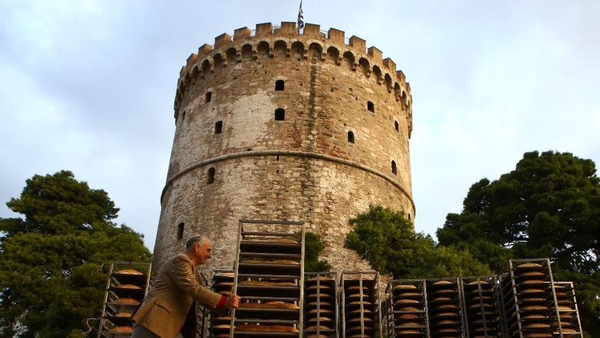 "Bakers put the final touches on a giant ""koulouri"" (bread ring similar to a bagel or pretzel) that encircled the medieval White Tower, in the northern Greek port city of Thessaloniki on Sunday, October 19, 2014. The 165-m (540-ft) diameter product weighed 1.35 tons before baking. The bakers next plan to build a ring bread around the burial ground in Amphipolis, northeast of Thessaloniki. (AP Photo/Grigoris Siamidis)"