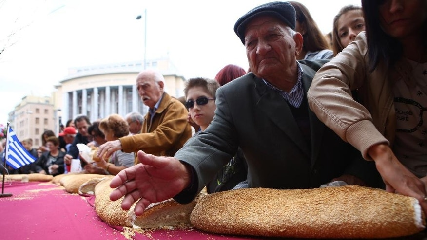 "People wait to get ""koulouri"" (bread ring similar to a bagel or pretzel) that encircled the medieval White Tower, in the northern Greek port city of Thessaloniki on Sunday, October 19, 2014. The 165-m (540-ft) diameter product weighed 1.35 tons before baking. The bakers next plan to build a ring bread around the burial ground in Amphipolis, northeast of Thessaloniki. (AP Photo/Grigoris Siamidis)"
