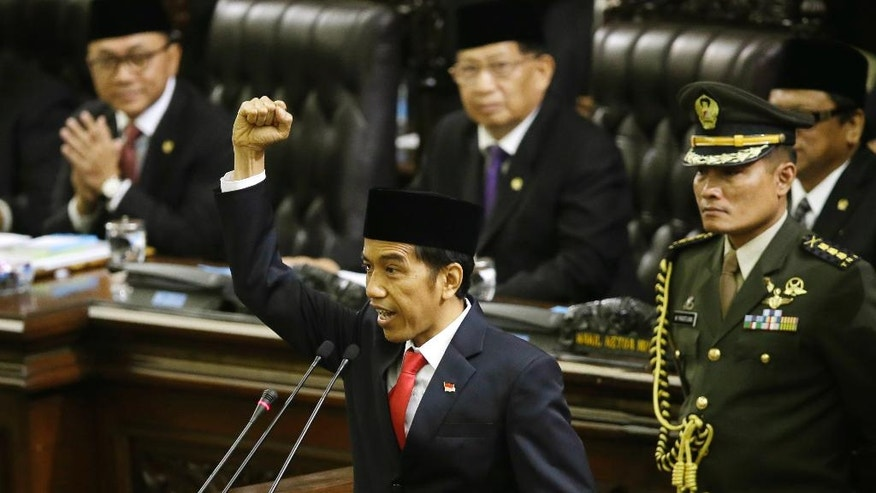"Indonesian President Joko Widodo, center, shouts ""freedom"" while raising his fist as he delivers his speech during his inauguration ceremony as the country's seventh president at the parliament building in Jakarta, Indonesia, Monday, Oct. 20, 2014.  (AP Photo/Dita Alangkara)"
