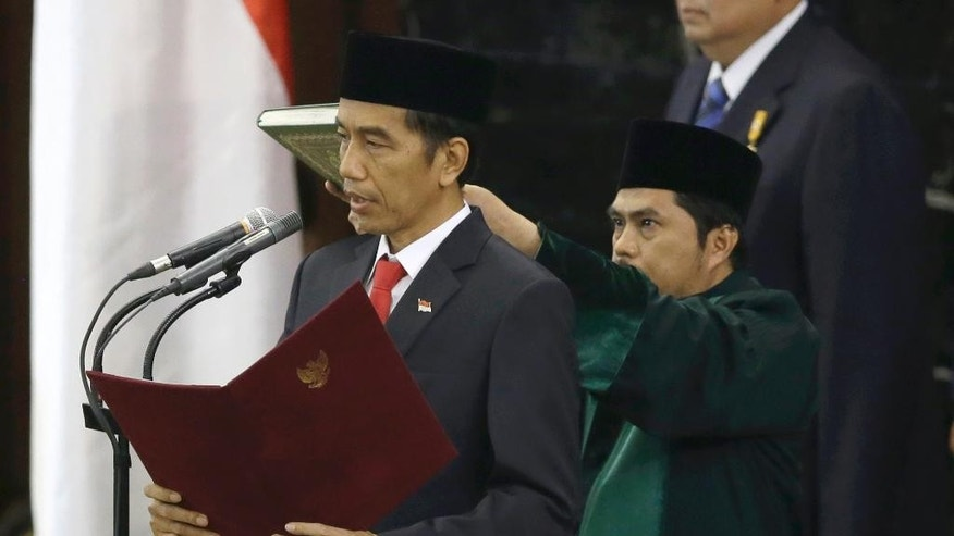 Indonesian President Joko Widodo, center, reads his oath during his inauguration ceremony as the country's seventh president at the parliament building in Jakarta, Indonesia, Monday, Oct. 20, 2014. (AP Photo/Dita Alangkara)