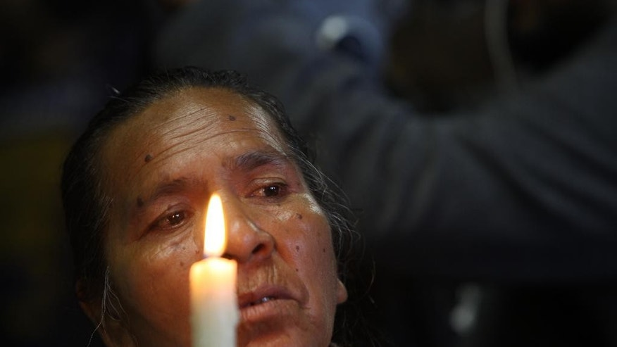 A mother of one of 43 missing students from the Isidro Burgos rural teachers college attends a mass at the Basilica of Guadalupe in Mexico City, Sunday, Oct. 19, 2014. Investigators determined that 28 sets of human remains recovered from a mass grave discovered last weekend outside Iguala, in Guerrero state, were not those of any of the youths who haven't been seen since being confronted by police in that city Sept. 26. (AP Photo/Marco Ugarte)