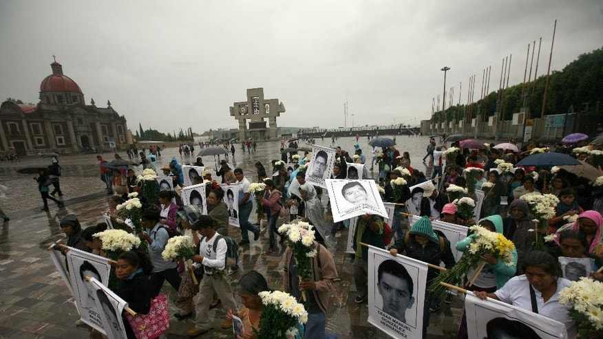 Mothers and relatives of the 43 missing students from the Isidro Burgos rural teachers college, with posters with the images of their missing loved ones walk in to attend a mass at the Basilica of Guadalupe in Mexico City, Sunday, Oct. 19, 2014. Investigators determined that 28 sets of human remains recovered from a mass grave discovered last weekend outside Iguala, in Guerrero state, were not those of any of the youths who haven't been seen since being confronted by police in that city Sept. 26. (AP Photo/Marco Ugarte)