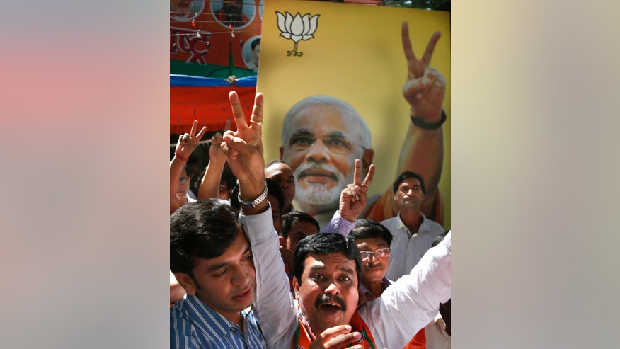 Supporters of India's ruling Bharatiya Janata Party (BJP) celebrate as early results indicated the party leading in the Maharashtra state Assembly elections in Mumbai, India, Sunday, Oct. 19, 2014. Prime Minister Narendra Modi's (photograph behind) BJP party appeared poised to make huge election gains Sunday in Haryana and Maharashtra states which went to polls Wednesday.(AP Photo/Rafiq Maqbool)
