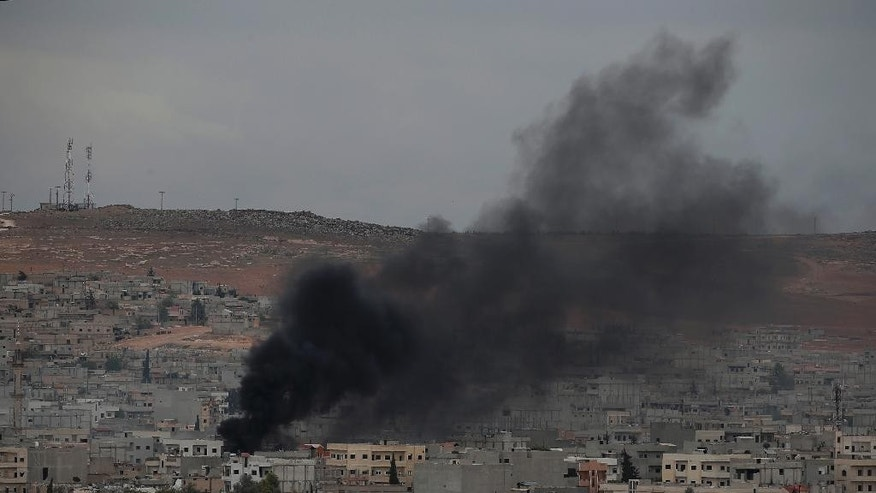 Smoke from a fire rises following a strike in Kobani, Syria, during fighting between Syrian Kurds and the militants of Islamic State group, as seen from a hilltop on the outskirts of Suruc, at the Turkey-Syria border, Sunday, Oct. 19, 2014. Kobani, also known as Ayn Arab, and its surrounding areas, has been under assault by extremists of the Islamic State group since mid-September and is being defended by Kurdish fighters. (AP Photo/Lefteris Pitarakis)