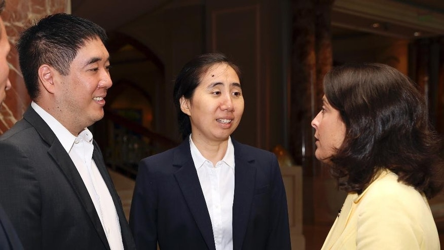 U.S. Ambassador to Qatar, Dana Shell Smith, from right, speaks with American couple Grace and Matthew Huang, sentenced to jail over charges they starved their 8-year-old adopted daughter to death, as they meet at a hotel in Doha, Qatar, Sunday, Oct. 19, 2014. The American couple were released from prison in November, but were banned from leaving Qatar during their trial. Their appeal begins on Monday. (AP Photo/Osama Faisal)