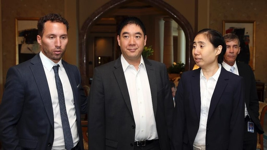 A lawyer, from left, meets with American couple Matthew and Grace and Huang, sentenced to jail over charges they starved their 8-year-old adopted daughter to death, at a hotel in Doha, Qatar, Sunday, Oct. 19, 2014. The American couple were released from prison in November, but were banned from leaving Qatar during their trial. Their appeal begins on Monday. (AP Photo/Osama Faisal)