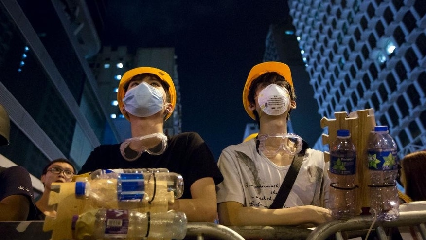 Protesters wear protective gear made by plastic bottle at a barricade in the Mong Kok district of Hong Kong, early Monday, Oct. 20, 2014. Three weeks ago, students at a rally stormed a fenced-off courtyard outside Hong Kong's government headquarters, triggering unprecedented mass protests for greater democracy in the semiautonomous Chinese city. (AP Photo/Kin Cheung)