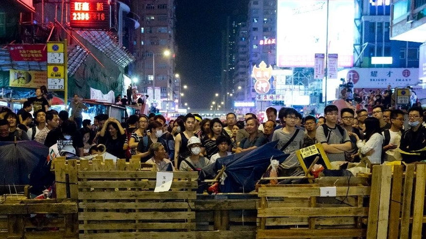 Protesters stand guard behind a barricade at the occupied area in the Mong Kok district of Hong Kong, early Monday, Oct. 20, 2014. Three weeks ago, students at a rally stormed a fenced-off courtyard outside Hong Kong's government headquarters, triggering unprecedented mass protests for greater democracy in the semiautonomous Chinese city. (AP Photo/Kin Cheung)