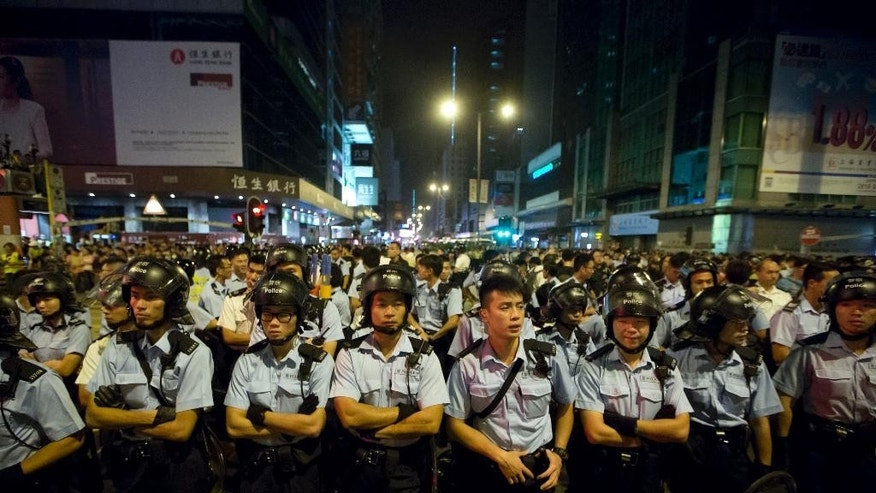 Riot police stand guard at the occupied area in the Mong Kok district of Hong Kong, early Monday, Oct. 20, 2014. Three weeks ago, students at a rally stormed a fenced-off courtyard outside Hong Kong's government headquarters, triggering unprecedented mass protests for greater democracy in the semiautonomous Chinese city. (AP Photo/Kin Cheung)