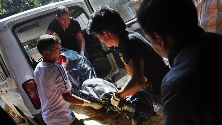 Hospital personnel with the help of the relatives of the avalanche victims, shift the body of a victim onto a stretcher at a morgue at Teaching Hospital in Katmandu, Nepal, Monday, Oct. 20, 2014. Nepal was wrapping up rescue operations in its northern mountains Monday, saying all the hikers believed to have been stranded on a trekking route by a series of deadly blizzards are now safe. (AP Photo/Niranjan Shrestha)