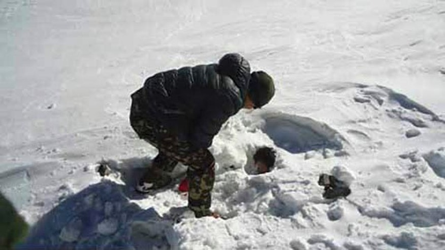 October 19, 2014: In this photo provided by the Nepalese army, a soldier searches for avalanche victims at Thorong La pass. (AP Photo/Nepalese Army)
