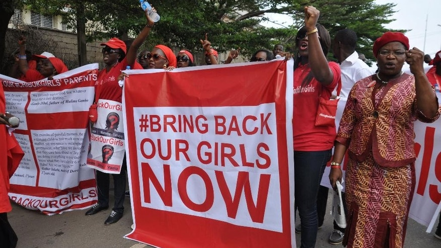 FILE - In this file photo taken Tuesday, Oct. 14, 2014, people demonstrate calling on the Nigerian government to rescue girls taken from a secondary school in Chibok  region, in the city of Abuja, Nigeria. There is cautious optimism in Nigeria,  Monday, Oct.  20, 2014 over local reports that the more than 200 abducted Nigerian schoolgirls may soon be released soon as part of a cease-fire agreement with the country's Islamic rebels, Boko Haram. (AP Photo/Olamikan Gbemiga, File)