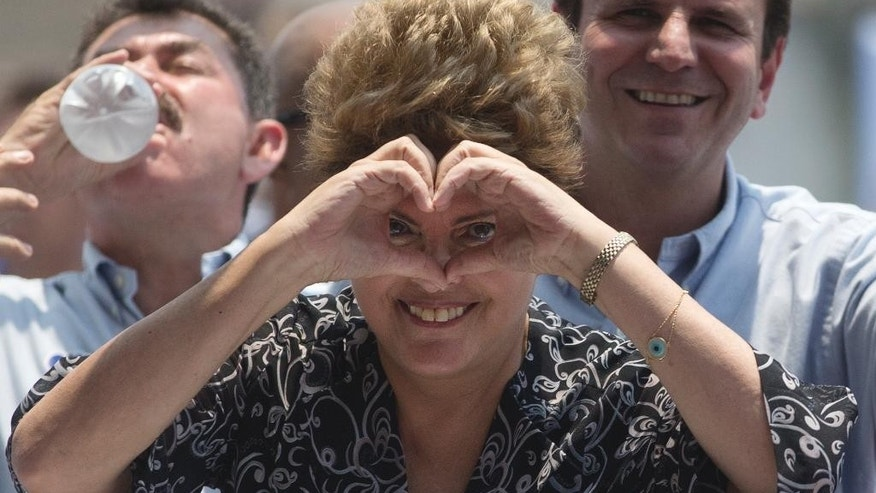 Brazil's President and Workers Party candidate Dilma Rousseff flashes a heart hand gesture during a rally for her re-election campaign in Rio de Janeiro, Brazil, Monday, Oct. 20, 2014. Rousseff and her challenger Aecio Neves of the Brazilian Social Democracy Party are in a tight election contest, that culminates Oct. 26 when upward of 140 million Brazilians are expected to go to the polls and decide who'll be the next leader of the globe's fifth most populous nation and Latin America's biggest economy.  (AP Photo/Silvia Izquierdo)