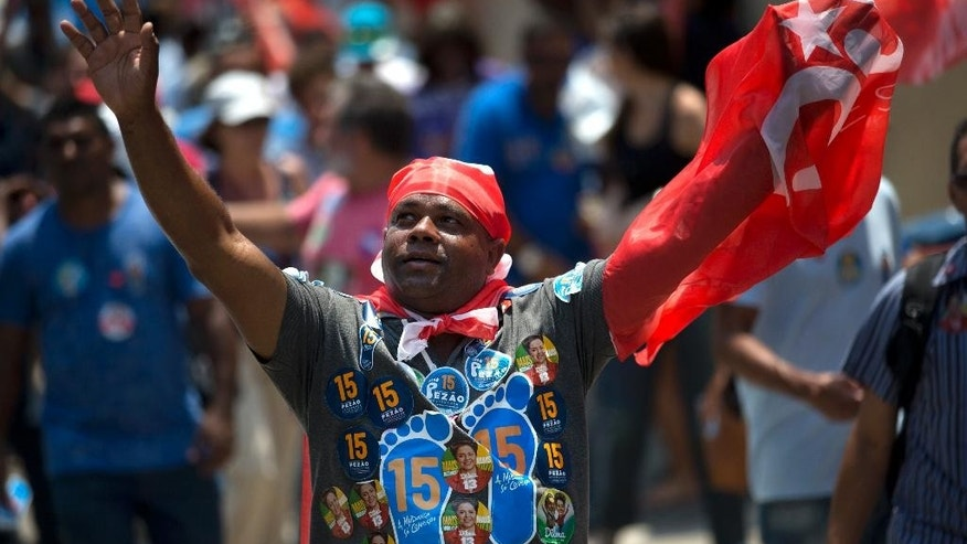A supporter of Brazil's President and Workers Party candidate Dilma Rousseff, attends a rally for Rousseff's re-election campaign in Rio de Janeiro, Brazil, Monday, Oct. 20, 2014. Incumbent Rousseff and her challenger Aecio Neves of the Brazilian Social Democracy Party are in a tight election contest, that culminates Oct. 26 when upward of 140 million Brazilians are expected to go to the polls and decide who'll be the next leader of the globe's fifth most populous nation and Latin America's biggest economy. (AP Photo/Silvia Izquierdo)