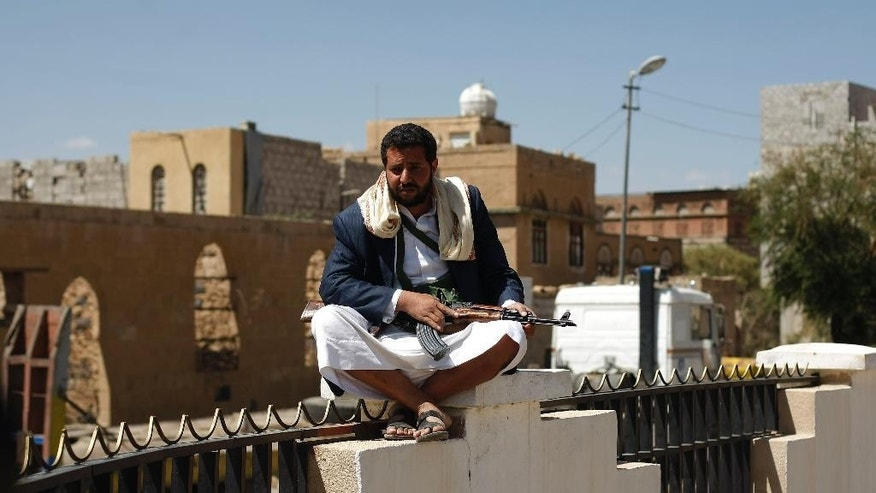 An armed Houthi Shiite rebel sits on a wall while guarding a street in Sanaa, Yemen, Monday, Oct. 20, 2014. Yemeni security officials said al-Qaida's Sunni militants seized al-Adeen town 200 kilometers (125 miles) south of the capital Sanaa in Ibb province. (AP Photo/Hani Mohammed)