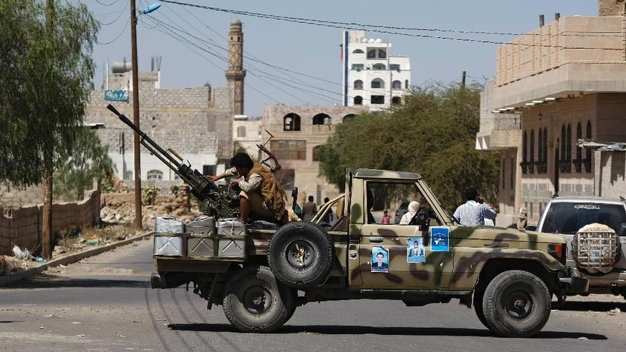 A Houthi Shiite rebel mans a machine gun mounted on a military truck in Sanaa, Yemen, Monday, Oct. 20, 2014. Yemeni security officials said al-Qaida's Sunni militants seized al-Adeen town 200 kilometers (125 miles) south of the capital Sanaa in Ibb province. (AP Photo/Hani Mohammed)