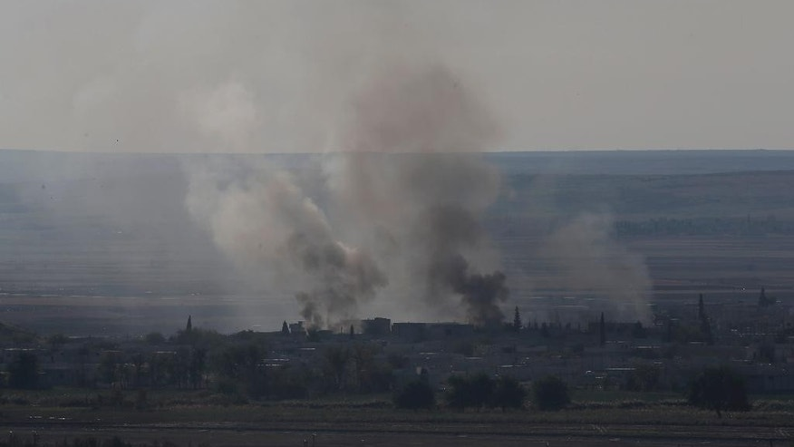 Smoke from fires rise over Kobani, Syria, during fighting between Syrian Kurds and the militants of Islamic State group, as seen from a hilltop on the outskirts of Suruc, at the Turkey-Syria border, Tuesday, Oct. 21, 2014. The buildings, bottom, are within Turkey.  Kobani, also known as Ayn Arab, and its surrounding areas, has been under assault by extremists of the Islamic State group since mid-September and is being defended by Kurdish fighters. (AP Photo/Lefteris Pitarakis)