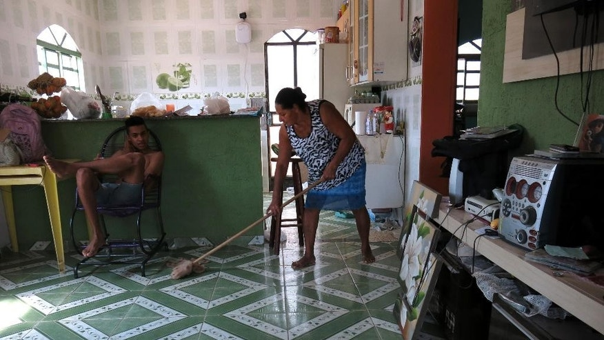 "In this Oct. 14, 2014 photo, Maria Lindaura Dos Santos, 64, right, sweeps her home in Belo Horizonte, Minas Gerais state, Brazil. Dos Santos lives in a poor rural area on the capital's outskirts with her daughter and three grandchildren. Water and electricity are connected, they still have no sewage system, but the new neighborhood is pulling through, she says. ""No one used to do anything for people in the villages. But we have a little house, and a bus stops nearby,"" said Dos Santos, a supporter of Brazil's President Dilma Rousseff and the Workers' Party. ""They are the only ones who remember we exist."" (AP Photo/Adriana Gomez)"
